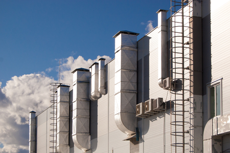 industrial building with ventilation pipes and air conditioners against the blue sky Editorial