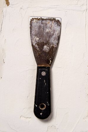 a vintage putty knife on the background of putty