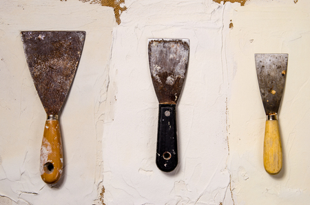 three different vintage putty knives on the background of putty Фото со стока