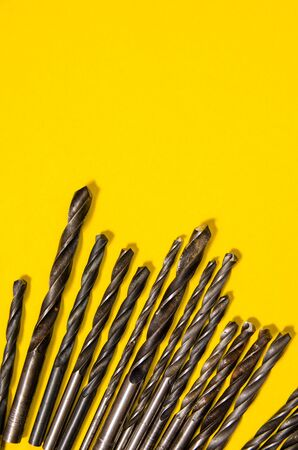 a lot of drills of different sizes on a bright yellow background. vertical view. Stock Photo