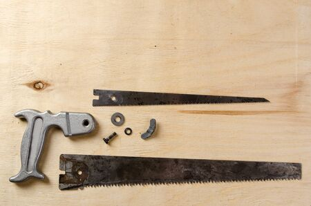 disassemble hand saw lying on a sheet of plywood. flat view.