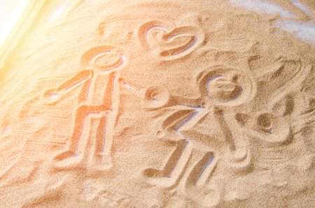 drawn on the sand figures of a man and a woman with a symbol of the heart above them