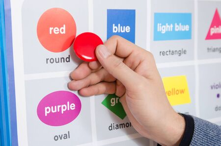 a male educator explains the spelling of the word red on the training table in the training room