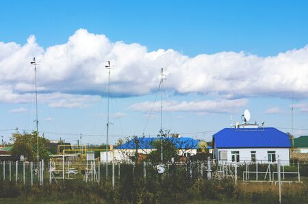 meteorological station with house on a background of blue sky with white clouds 版權商用圖片
