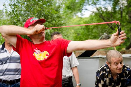 KOMSOMOLSK-ON-AMUR, RUSIA, 1 DE AGOSTO DE 2015. Día del ferroviario abierto al público. Hombre de rojo dispara desde un tirachinas en competiciones