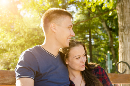 smiling loving couple sitting on bench in park looking in same direction Standard-Bild