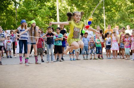 Komsomolsk am Amur, Russland - 1. August 2016. Öffentlicher Tag des Eisenbahners. Mädchen springt über ein Seil, das von Mädchen in Piratenkostümen auf einer Piratenparty gehalten wird