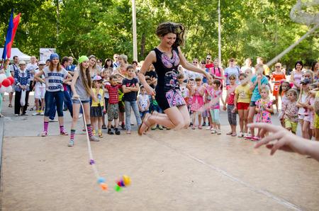 Komsomolsk am Amur, Russland - 1. August 2016. Öffentlicher Tag des Eisenbahners. Erwachsene Frau springt über ein Seil, das Mädchen in Piratenkostümen auf der Piratenparty halten. Mama spielt mit Kindern Editorial