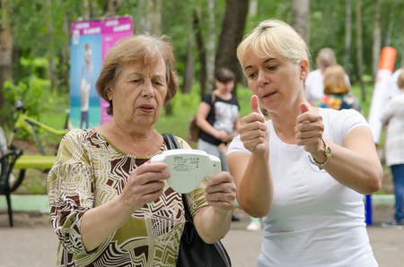 Komsomolsk-on-Amur, Russia - August 19, 2018. female volunteer shows elderly woman how to properly hold body fat monitor in her hands Editoriali