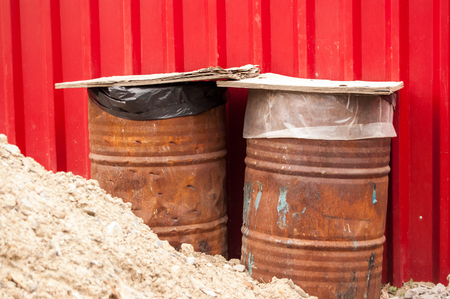 two metal rusty barrels covered with boards against red metal wall.