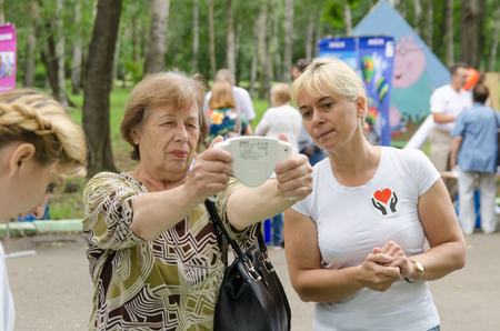 Komsomolsk-on-Amur, Russia - August 19, 2018. elderly woman measures body fat monitor in her hands under the guidance of female volunteer