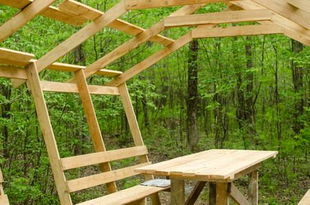 construction of wooden canopy with table and benches in the forest