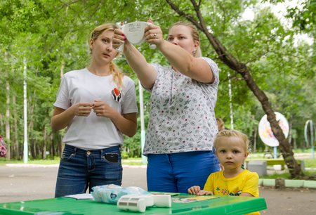 Komsomolsk-on-Amur, Russia - August 19, 2018. women plus size measures body fat with monitor under the guidance of female volunteer. pretty fatty overweigt woman with monitor body fat in her hands Editorial
