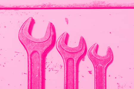 several wrenches on the background of metal painted plates. pink toned. concept of feminism.