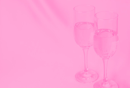 two glasses of champagne on background of fabric. pink toned. Stock Photo