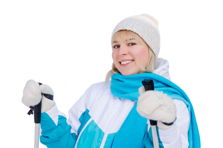 attractive blonde girl in sports jacket, hat and blue scarf and ith ski poles in her hands with smile looking at the camera. isolated on white background. healthy lifestyle concept. nature walks in winter. pleasure from walk on skis.