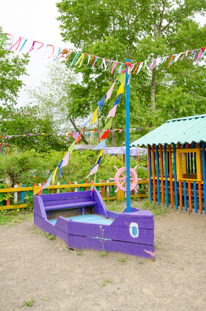 wooden violet boat with coloful flags on sandy playground.