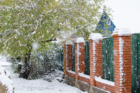 brick-iron fence covered with snow in private area during snowfall in winter.