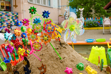lot of childrens multi-colored shovels with bucket in sandbox on the playground in summer day.