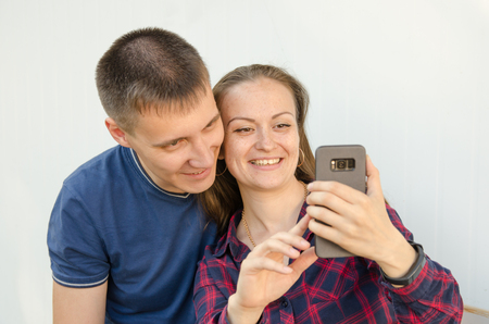 guy with short haircut in blue T-shirt and s,iling girl with dark long hair in red and blue checkered shirt take selfie on the phone.