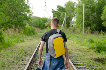 young man in jeans with backpack on his back goes forward along abandoned railway.