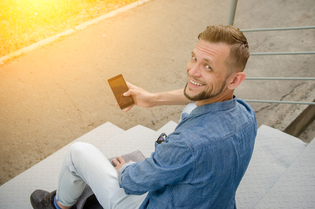 young man in jeans and a denim shirt is sitting on the stairs with a smartphone in his hand turned around with smiling and looks directly at camera.