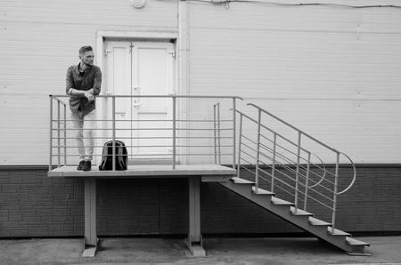 bearded young man in jeans and a denim shirt is standing on the porch of an industrial building near a closed door. job search or firing concept.