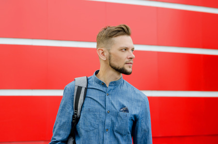 young serious bearded man in denim shirt against the background of red wall. Фото со стока