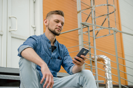 young man in jeans and a denim shirt is sitting on the stairs of an industrial building with a smartphone in his hand. Stock Photo