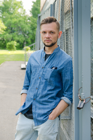 serious bearded young man in denim shirt and with his hands in his pockets stands near background of chain-link and looks straight into the camera.