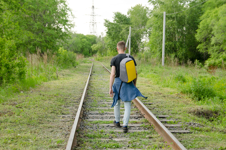 young man in jeans with backpack on his back goes forward along abandoned railway. concept of traveling alone. Stock Photo