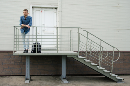 bearded young man in jeans and a denim shirt is standing on the porch of an industrial building near a closed door. firing concept. Stock Photo