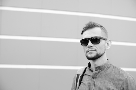 young serious bearded man in sunglasses and denim shirt against the background of wall. Stock Photo