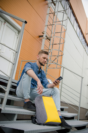 young man in jeans and a denim shirt is sitting on the stairs of an industrial building with a smartphone in his hand next to his backpack while waiting.