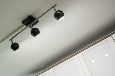 black triple directional luminaire with ceiling mount.
