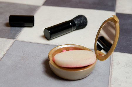 powder box with mirror and makeup brush on black and white checkered background. side view Stockfoto