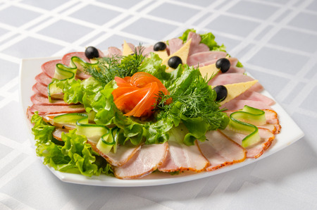 banquet cutting with ham, meat delicacies, cheese, sausage smoked, olive, lettuce and tomato on white dish. Stock Photo
