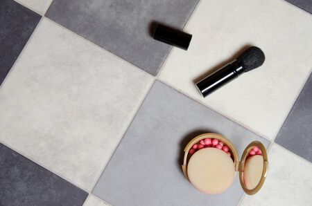 powder box with mirror and makeup brush on black and white checkered background.