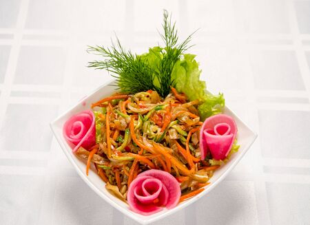 salad of pork ears, carrots, Bulgarian pepper, fresh cucumbers, lettuce, onions and greens seasoned with vegetable oil. Stock Photo