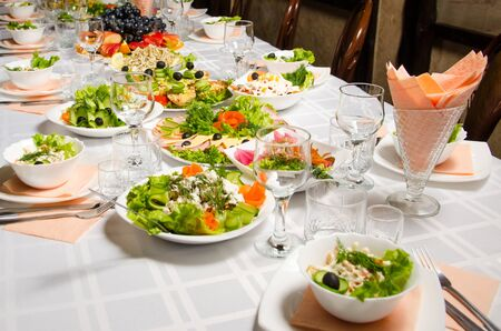 table lined with variety of dishes from which the centerpiece is dish with banquet cutting with ham and dish with several tartlets with chicken and ham. Stock Photo