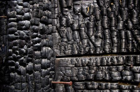 Black burnt wall of house of wooden planks with embossed texture. damage to the building from fire without the possibility of restoration. property insurance. Stock Photo