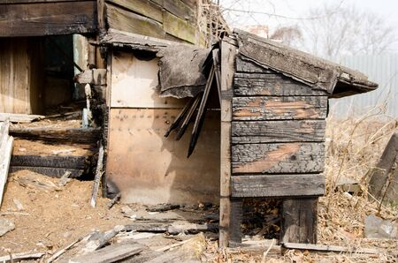 Brown and black burnt house of wooden planks with embossed texture without door and broken wall.  damage to the building from fire without the possibility of its restoration. concept of loss of real estate or home. property insurance.