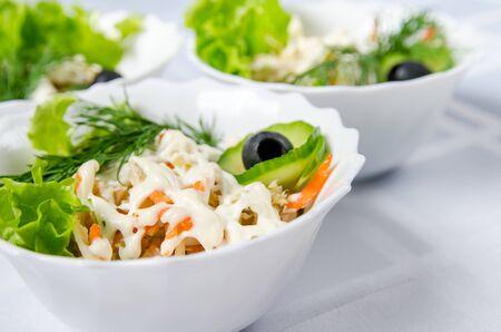 Ensalada de pollo hervido con calamares, pepinos encurtidos, mayonesa, zanahoria, lechuga, verduras y aceitunas en un plato blanco. Foto de archivo