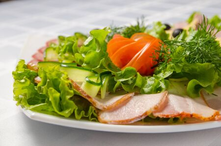 banquet cutting with ham, meat delicacies, cheese, sausage smoked, olive, lettuce and tomato on white dish. Reklamní fotografie