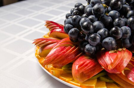 sliced fruit - apples, oranges, kiwi topped with grapes on white dish.