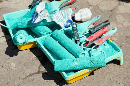 several paint rollers covered with green paint are in the tray.