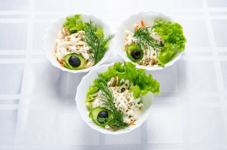 boiled chicken salad with squid, pickled cucumbers, mayonnaise, carrots, lettuce, greens and olive in white dish.