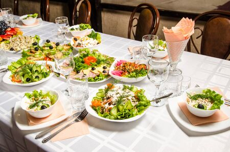 table lined with variety of dishes from which the centerpiece is dish with banquet cutting with ham and dish with several tartlets with chicken and ham. Reklamní fotografie