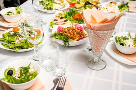 table lined with variety of dishes from which the centerpiece is dish of salad of pork ears, carrots, Bulgarian pepper, fresh cucumbers, lettuce, onions and greens seasoned with vegetable oil.
