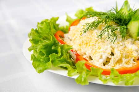 seafood salad - squid, crab sticks, cucumbers, eggs, mayonnaise, cheese, lettuce, tomato, olives and greens on white dish.